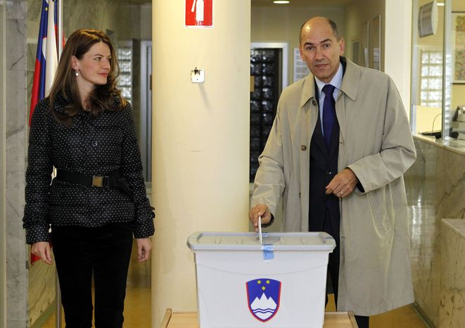 Opposition leader Janez Jansa casts his ballot as his wife, Urska Bacovnik, looks on at a polling station in Velenje, Slovenia, on Sunday, Dec. 4, 2011. (AP Photo)