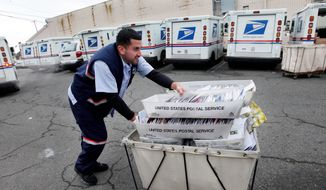 A letter carrier for the U.S. Postal Service moves a cart of mail to his truck. (Associated Press)