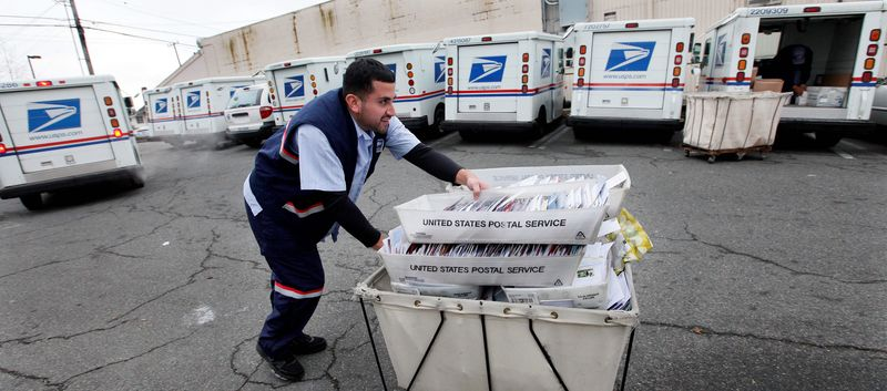 A letter carrier for the U.S. Postal Service moves a cart of mail to his truck. (