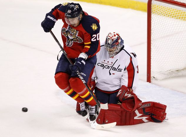 Florida Panthers left wing Sean Bergenheim (20) leaps as a teammate shoots towards Washington Capitals goalie Michal Neuvirth (30) during the second period of an NHL game, Monday, Dec. 5, 2011, in Sunrise, Fla. (AP Photo/Wilfredo Lee)