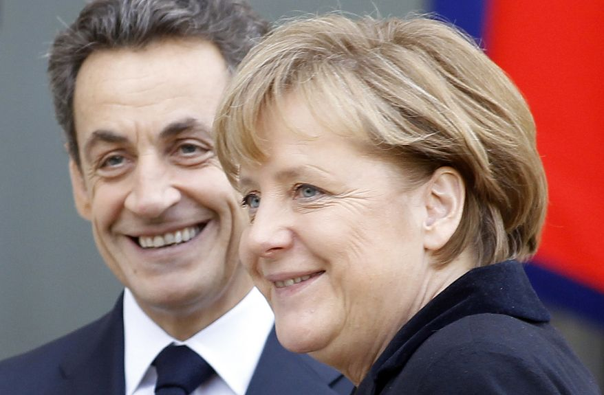 French President Nicolas Sarkozy greets German Chancellor Angela Merkel before their meeting at the Elysee Palace in Paris on Monday, Dec. 5, 2011. (AP Photo/Remy de la Mauviniere)