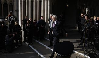 Julian Assange, founder of WikiLeaks, leaves the High Court in London on Monday, Dec. 5, 2011, after the court gave him permission to continue his legal battle to avoid extradition to Sweden over sex-crimes allegations. (AP Photo/Kirsty Wigglesworth)