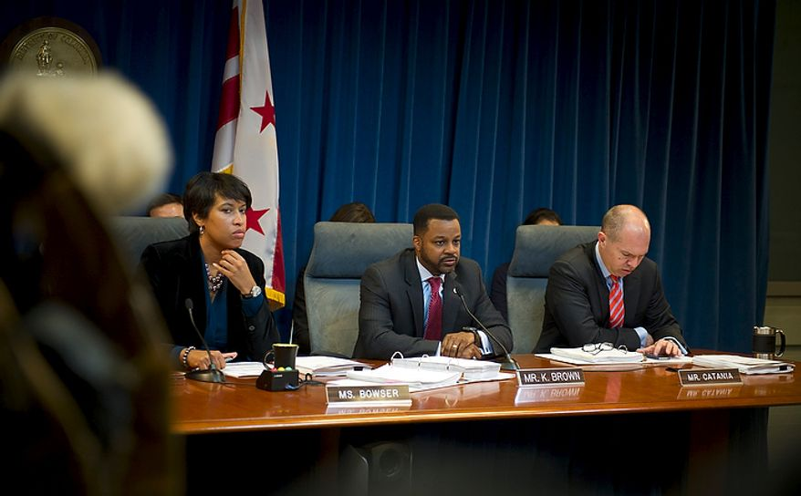 D.C. Council Chairman Kwame R. Brown (center) is seated between Committee on Government Operations Chairman Muriel Bowser (left) and council member David A. Catania (right) during a committee hearing in which a wide-ranging ethics-reform bill was advanced to the full council.