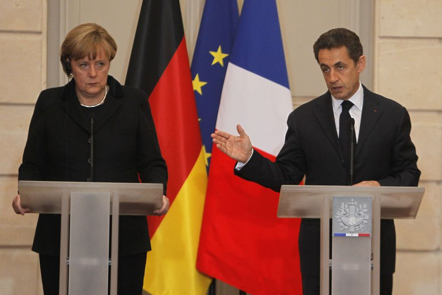German Chancellor Angela Merkel, left, and France's President Nicolas Sarkozy, right, speak to the media during a joint press conference at the Elysee Palace in Paris, Monday , Dec. 5, 2011. (AP Photo/Michel Euler)