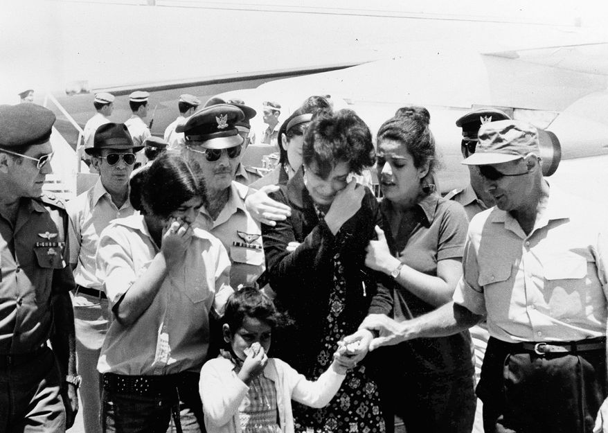 Israeli Defense Minister Moshe Dayan (right) comforts the family of slain military attache Joseph Alon on July 2, 1973.  (Associated Press)