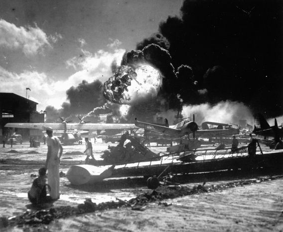 Sailors stand among wrecked airplanes at Ford Island Naval Air Station as they watch the explosion of the USS Shaw in the background, during the Japanese surprise attack on Pearl Harbor, Haw