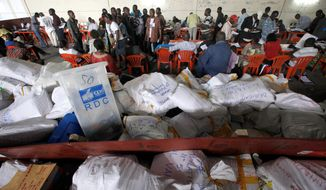 Election volunteers tabulate results Sunday in Kinshasa, Congo. The tallies Tuesday showed President Joseph Kabila apparently winning a second term, but there were also charges of fraud and threats of massive protests. (Associated Press)