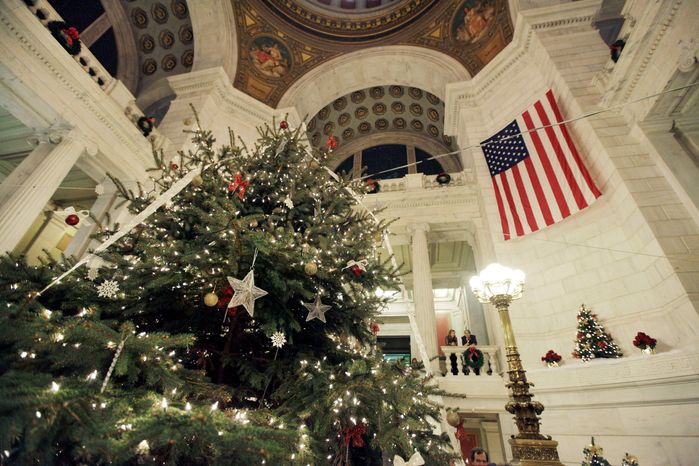 """Greenery referred to as a """"holiday tree"""" by Gov. Lincoln Chafee is lit Tuesday in the statehouse in Providence, R.I. Mr. Chafee and Republican state Rep. Doreen Costa battled over whether to call the official spruce a """"holiday"""" tree or a """"Christmas"""" tree. (Associated Press)"""