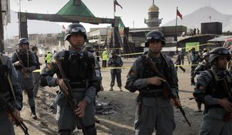 Afghan police officers stand guard at the scene of a suicide attack in Kabul, Afghanistan, Tuesday, Dec. 6, 2011. (AP Photo/Musadeq Sadeq)