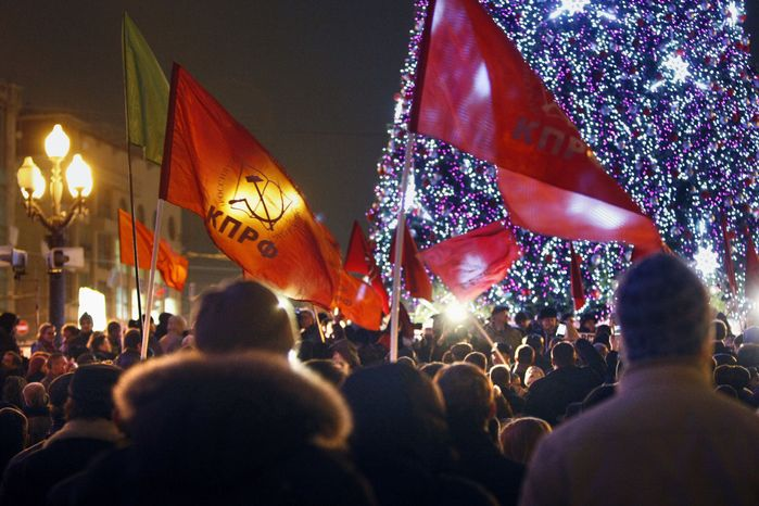 Russian Communist Party supporters hold flags with the party colors and emblem during a demonstration in Moscow on Monday, Dec. 5, 2011, to protest the official results of parliamentary elections. (AP Photo/Alexander Zemlianichenko)