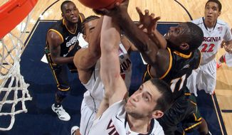 Virginia guard Sammy Zeglinski (13) reaches for the rebound with George Mason guard Vertrail Vaughns (11) during the second half of an NCAA basketball game Tuesday, Dec. 6, 2011, in Charlottesville, Va. Virginia won 68-48. (AP Photo/Andrew Shurtleff)