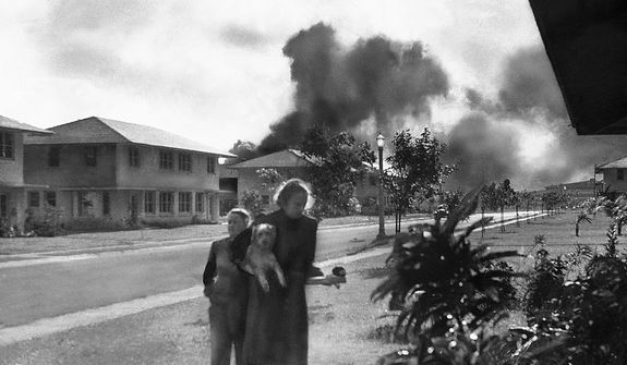 "Officers' wives, investigating explosion and seeing smoke pall in distance on Dec. 7, 1941, heard neighbor Mary Naiden, then an Army hostess who took this picture, exclaim ""There are red circles on those planes overhead. They are Japanese!"" Realizing war had come, the two women, stunned, start toward quarters. (AP Photo/Mary Naiden)"