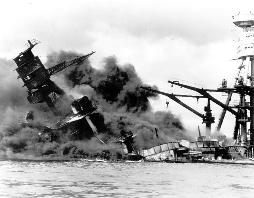 In this  Dec. 7, 1941 file picture, the battleship USS Arizona belches smoke as it topples over into the sea during a Japanese surprise attack on Pearl Harbor, Hawaii. (AP Photo)