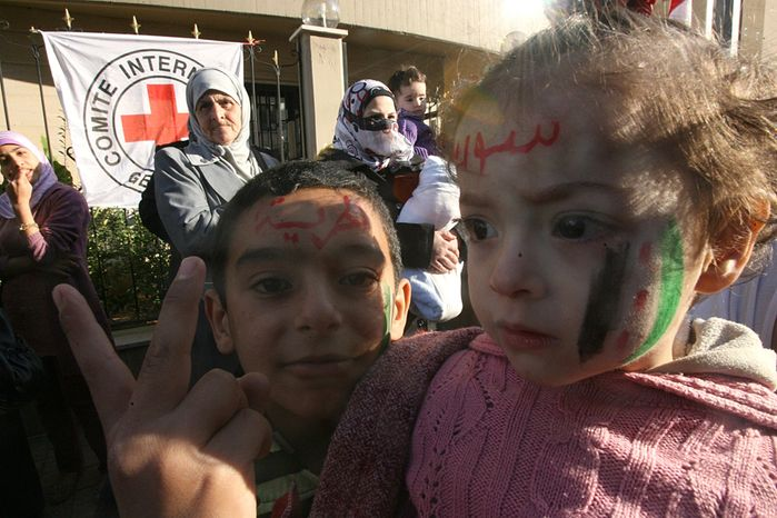 """** FILE ** Two Syrian refugees children who fled violence in their country flash a V for victory sign while their faces faces are decorated with the Syrian revolution flag and Arabic words read:""""Syria, The freedom,"""" during a demonstration in front of the International Committee of the Red Cross office, in the northern city of Tripoli, Lebanon, on Friday Nov. 25, 2011. (AP Photo)"""