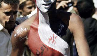 """A Yemeni protester wears the colors of his national flag painted on his body and an Arabic phrase that reads, """"The people want the butcher to be executed,"""" during a rally to demand the prosecution of President Ali Abdullah Saleh in Sanaa, Yemen, on Wednesday. (Associated Press)"""