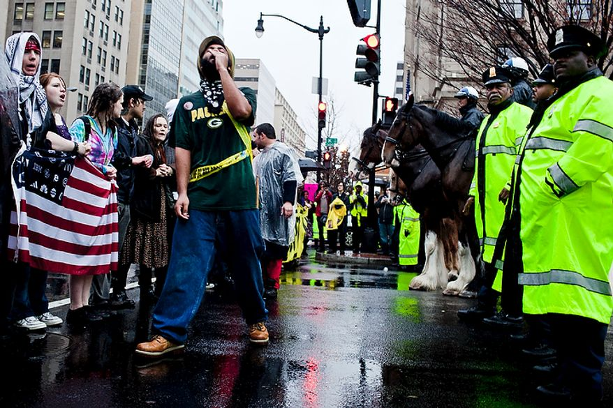 Occupy DC protestors stand off with police as they block the intersection of 14th St. NW and K St. NW in Washington, D.C. on Dec. 7, 2011. (T.J. Kirkpatrick/ The Washington Times)