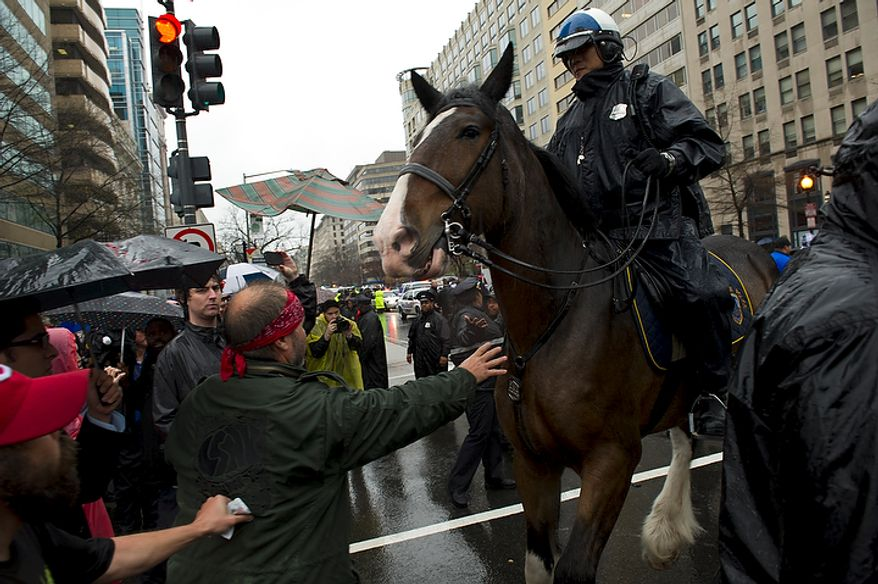 A man reaches out to brace himself against a police horse as Washington D.C. Metro police clear the street and make arrests during a protest in the intersection of 14th and K Streets NW in Washington, D.C., Wednesday, December 7, 2011. Police also used horses to try to keep order in this situation. (Rod Lamkey Jr./The Washington Times)