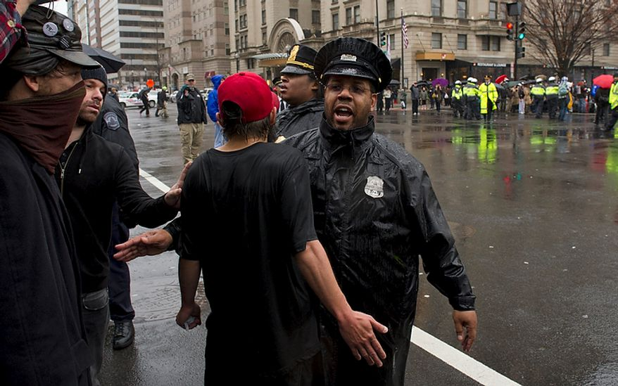 A man has words with a Washington D.C. Metro police officer as they try to clear the street and make arrests during a protest in the intersection of 14th and K Streets NW in Washington, D.C., Wednesday, December 7, 2011. Police also used horses to try to keep order in this situation. (Rod Lamkey Jr./The Washington Times)