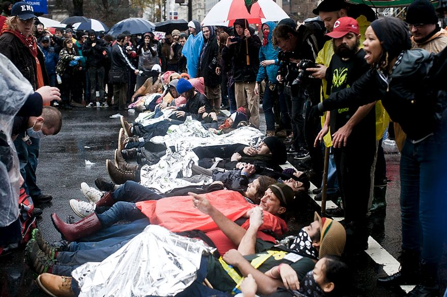 Occupy DC protestors lie down across K St. NW at the intersection with  14th St. NW in Washington, D.C. on Dec. 7, 2011. (T.J. Kirkpatrick/ The Washington Times)