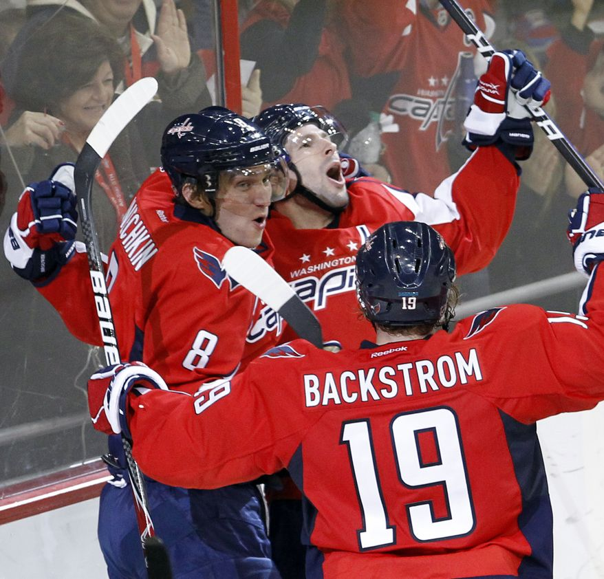Washington Capitals' Alex Ovechkin  and Nicklas Backstrom congratulate teammate Troy Brouwer after he scored on Ottawa Senators goalie Craig Anderson during the third period of an NHL hockey game in Washington, Saturday, Dec. 3, 2011. The Capitals defeated the Senators 3-2 in overtime. (AP Photo/Ann Heisenfelt)