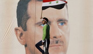 ** FILE ** A pro-Syrian regime protester waves a Syrian flag as he stands in front of portrait of Syrian President Bashar Assad, during a protest against sanctions, Damascus, Syria, in this Dec. 2, 2011, file photo. (AP Photo/Muzaffar Salman, File)