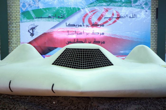 "This photo released on Thursday, Dec. 8, 2011, by the Iranian Revolutionary Guard and taken at an undisclosed location claims to show the U.S. RQ-170 Sentinel drone that Tehran says its forces downed earlier in the week. The banner in the background depicts an Iranian flag over which the text reads: ""God is great,"" ""Down with America,"" ""Down with Israel,"" ""Down with England."" (AP Photo/Sepahnews)"