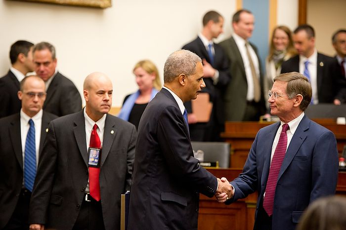 "U.S. Attorney General Eric Holder greets Congressman Lamar Smith (R-Tex.), right, as he appears before the House Judiciary Committee to answer questions about ""Fast and Furious"" a federal gun sting which allowed weapons to go to Mexican drug cartels through straw buyers, Thursday, December 8, 2011. (Andrew Harnik / The Washington Times)"