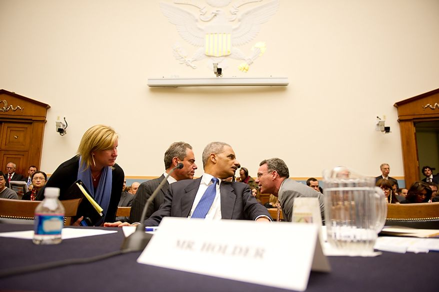 """U.S. Attorney General Eric Holder, center, talks with staff members before testifying in front of the House Judiciary Committee to answer questions about """"Fast and Furious"""" a federal gun sting which allowed weapons to go to Mexican drug cartels through straw buyers, Thursday, December 8, 2011. (Andrew Harnik / The Washington Times)"""