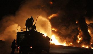 Pakistani firefighters try to extinguish burning NATO oil tankers after they were torched by militants at a terminal on the outskirts of Quetta, Pakistan, on Thursday, Dec. 8, 2011. (AP Photo/Arshad Butt)