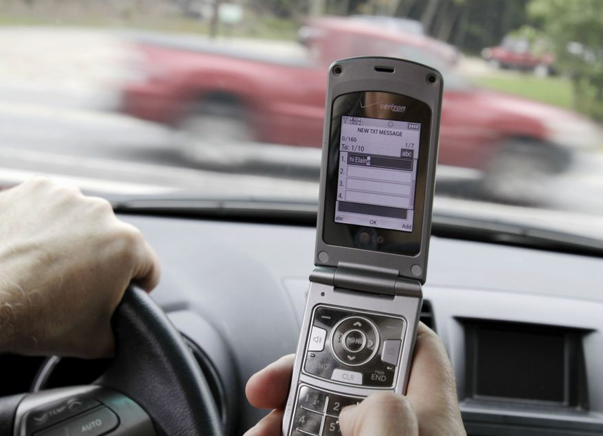 ** FILE ** In this Sept. 20, 2011, file photo, a phone is held in a car in Brunswick, Maine. Texting while driving increased 50 percent last year and two out of 10 drivers say they've sent text messages or emails while behind the wheel despite a rush by states to ban the practice, the National Traffic Safety Administration said Thursday. (AP Photo/Pat Wellenbach, File)