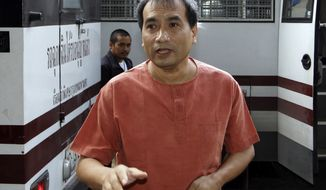 Thai-born American Joe Gordon answers a reporter's question upon his arrival at a criminal court in Bangkok on Thursday, Dec. 8, 2011. (AP Photo/Apichart Weerawong)