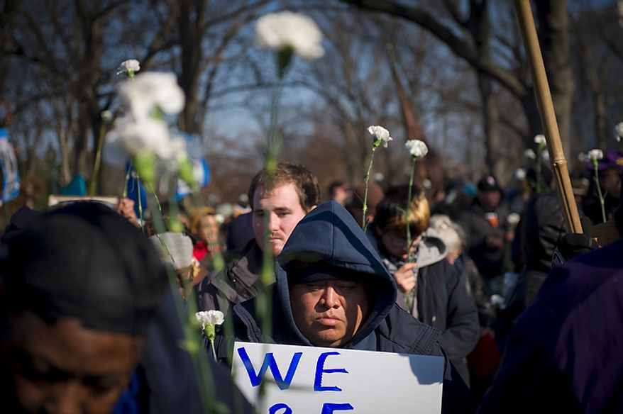 Across the street from the United States Capitol, an unidentified man stands among the white carnations and signs as he joins people from organizations from across the United States such as the Service Employees International Union (SEIU) at Upper Senate Park in Washington, D.C., Thursday, December 8, 2011, for an Interfaith Service for the Jobless, with unemployed workers and faith leaders. They are calling on Congress not to cut jobs and for the extension of unemployment insurance, which is set to expire at the end of the year unless Congress takes action. (Rod Lamkey Jr./The Washington Times)