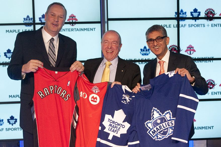 George Cope, left, President and CEO of Bell Canada, Maple Leafs Sports & Entertainment Chairman Larry Tanenbaum, center, and Nadir Mohamed, President and CEO of Rogers Communications hold up Toronto Raptors, Toronto FC, Toronto Maple Leafs and Toronto Marlies jerseys following a news conference in Toronto on Friday Dec. 9, 2011. Canada's largest telecommunication companies have agreed to buy the NHL's Toronto Maple Leafs and NBA's Toronto Raptors in a deal worth about $1.3 billion. Rogers Communications and BCE Inc. announced Friday the purchase of Maple Leaf Sports and Entertainment from the Ontario Teachers' Pension Plan in one of the richest sports deal in North American history. The deal also includes the Toronto FC of Major League Soccer, a minor league hockey team, and the Leafs and Raptors TV stations. (AP Photo/The Canadian Press, Chris Young)