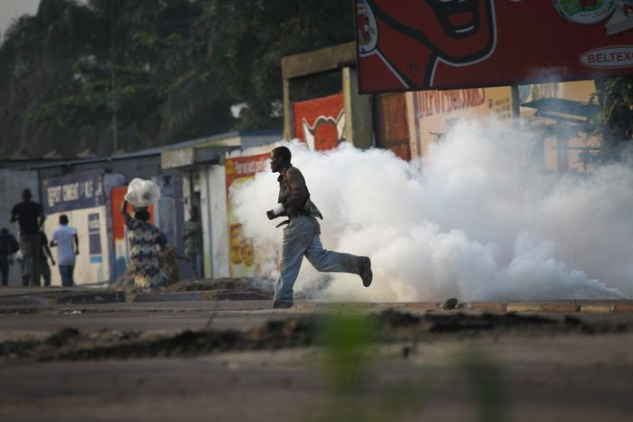 Congolese run from tear gas in the pro-Tshisekedi Matete commune in Kinshasa, Democratic Republic of Congo, Friday, Dec. 9, 2011, after the electoral commission declared Congolese President Joseph Kabila the winner. (AP Photo/Jerome Delay)