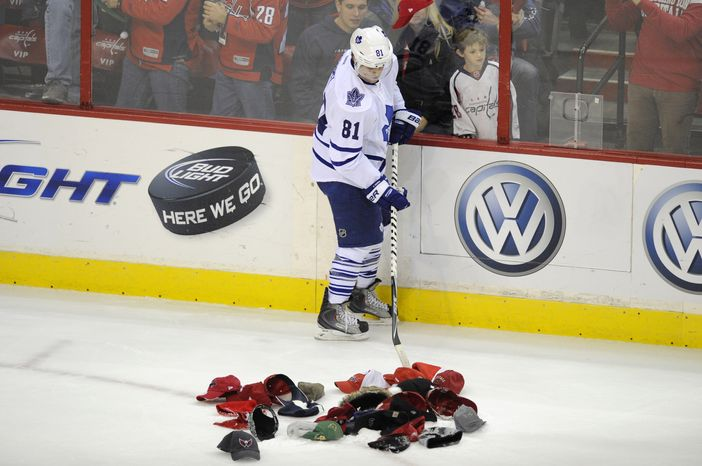 Toronto Maple Leafs right wing Phil Kessel helps collect hats that were thrown on the ice after Washington Capitals defenseman Dennis Wideman scored his third goal of the game during the third period, Friday, Dec. 9, 2011, in Washington. The Capitals won 4-2. (AP Photo/Nick Wass)