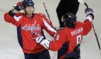 Washington Capitals defenseman Dennis Wideman celebrates his first of three goals with teammate Alex Ovechkin during the first period against the Toronto Maple Leafs on Friday, Dec. 9, 2011, in Washington. (AP Photo/Nick Wass)