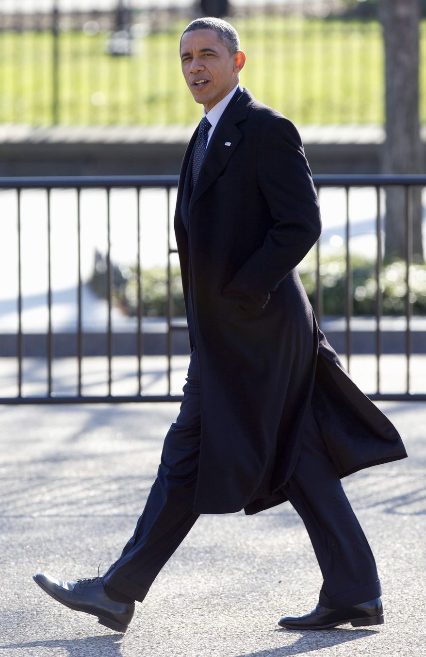 President Barack Obama walks across Pennsylvania Avenue from Blair House to the White House in Washington, Friday, Dec. 9, 2011, after visiting a holiday party. (AP Photo/Carolyn Kaster)