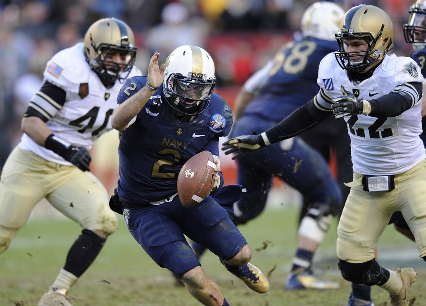 Navy quarterback Kriss Proctor rushes the ball as he is pressured by Army defenders Zach Watts and Nate Combs in the first half in Landover, Md., Saturday, Dec. 10, 2011. (AP Photo/Nick Wass)
