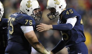 Navy center Brady DeMell shakes hands with kicker Jon Teague after Teague successfully kicked a field goal in the second half in Landover, Md., Saturday, Dec. 10, 2011. Navy won 27-21. (AP Photo/Nick Wass)