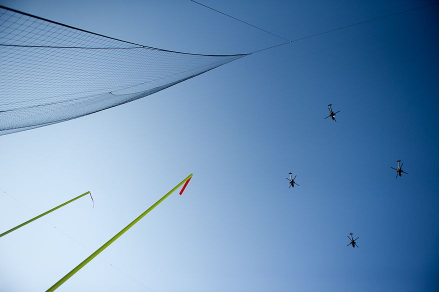 Helicopters fly over the field before the Army-Navy game at Fedex Field, Landover, MD, Saturday, December 10, 2011. (Andrew Harnik / The Washington Times)