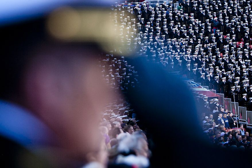 Navy midshipmen salute during the National Anthem as the Army-Navy game kicks off at FedEx Field in Landover, Md. on Dec. 10, 2011. Navy beat Army 27-21 for it's 10th win in a row. (T.J. Kirkpatrick/ The Washington Times)