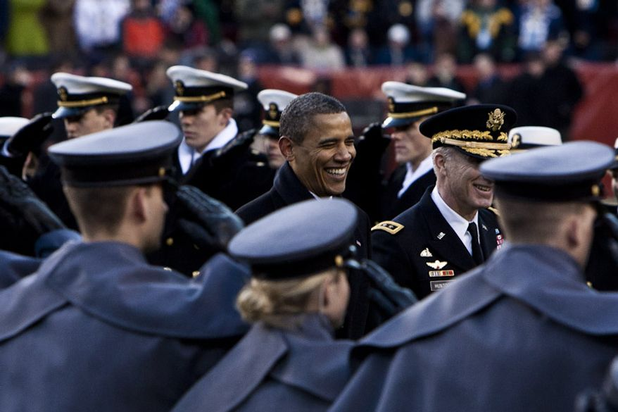President Barack Obama, at center, crosses the field to sit on the Army side during half time in the tied 14-14 Army-Navy game at FedEx Field in Landover, Md. on Dec. 10, 2011. (T.J. Kirkpatrick/ The Washington Times)