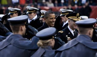 President Barack Obama, at center, crosses the field to sit on the Army side during half time in the tied 14-14 Army-Navy game at FedEx Field in Landover, Md., on Dec. 10, 2011. (T.J. Kirkpatrick/The Washington Times)