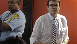 Greg Combet, minister for Climate Change Australia, right, walks out of the negotiation room as the climate change summit nears its end in the city of Durban, South Africa, Saturday, Dec. 10, 2011. Some ministers and top climate negotiators left Durban without an agreement Saturday. (AP Photo/Schalk van Zuydam)