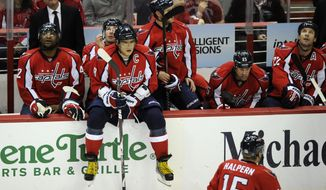Washington Capitals left wing Alex Ovechkin sits on top of the wall on the bench area during a break in the action against the Toronto Maple Leafs, Friday, Dec. 9, 2011, in Washington. (AP Photo/Nick Wass)