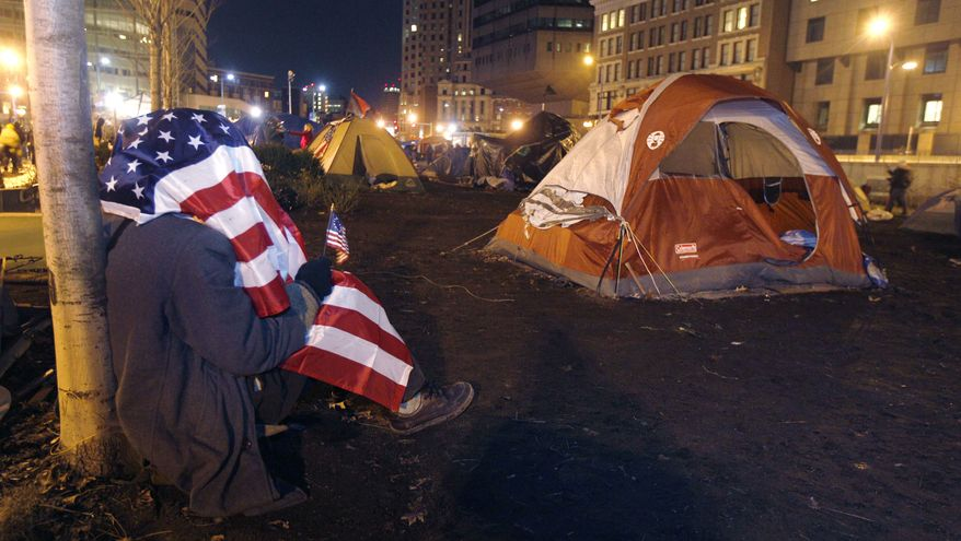 An Occupy Boston protestor wrapped in an American flag rests against a tree near open space where tents were set up in Dewey Square in Boston, early Friday Dec. 9, 2011. Boston Mayor Thomas Menino said Thursday that Occupy Boston protesters must leave their encampment in the city's financial district by midnight Thursday or face eviction by police. (AP Photo/Charles Krupa)