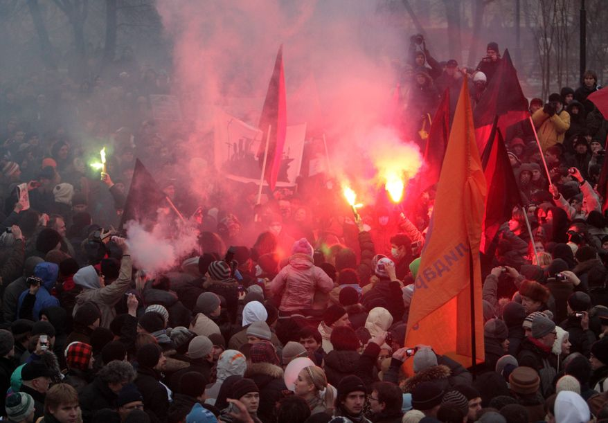 Protesters light flares during a mass rally against alleged vote rigging in Russia's parliamentary elections in Moscow on Saturday, Dec. 10, 2011. (AP Photo/Pavel Golovkin)