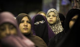 ** FILE ** Egyptian women listen during a Muslim Brotherhood campaign rally in Bashteil, a neighborhood of Cairo.(Associated Press)