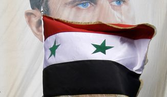 A Syrian flag flies in front of a large banner of President Bashar Assad as demonstrators rally in support of the Assad regime in Damascus, Syria, on Friday, Dec. 9, 2011. (AP Photo/Muzaffar Salman)