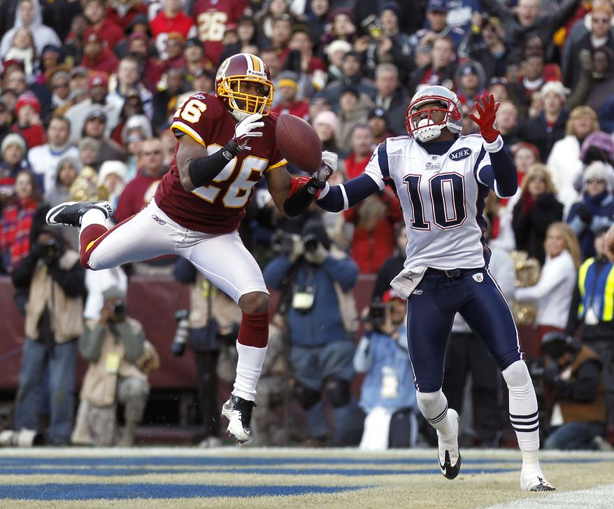 Washington Redskins cornerback Josh Wilson intercepts Tom Brady's pass intended for New England Patriots wide receiver Tiquan Underwood during the second half Sunday, Dec., 11, 2011, in Landover, Md. The Patriots won 34-27. (AP Photo/Pablo Martinez Monsivais)